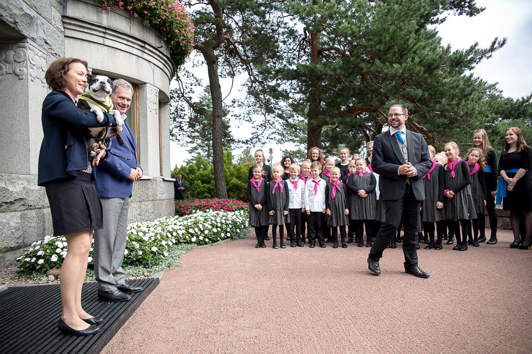 Myös Lennu-koira seurasi esitystä. Oikealla kuoron taiteellinen johtaja Pekka Nebelung. Kuva: Matti Porre/Tasavallan presidentin kanslia
