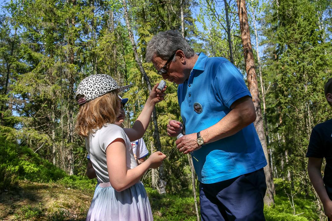 Presidentti nuuhkaisee Kaislan keräämiä kasveja tuoksupurkista. Kuva: Matti Porre/Tasavallan presidentin kanslia