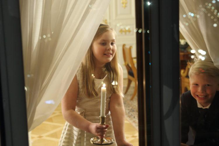 Barnen ställer ljus i fönstret i Gula salen i Presidentens slott. Foto: Juhani Kandell/Republikens presidents kansli